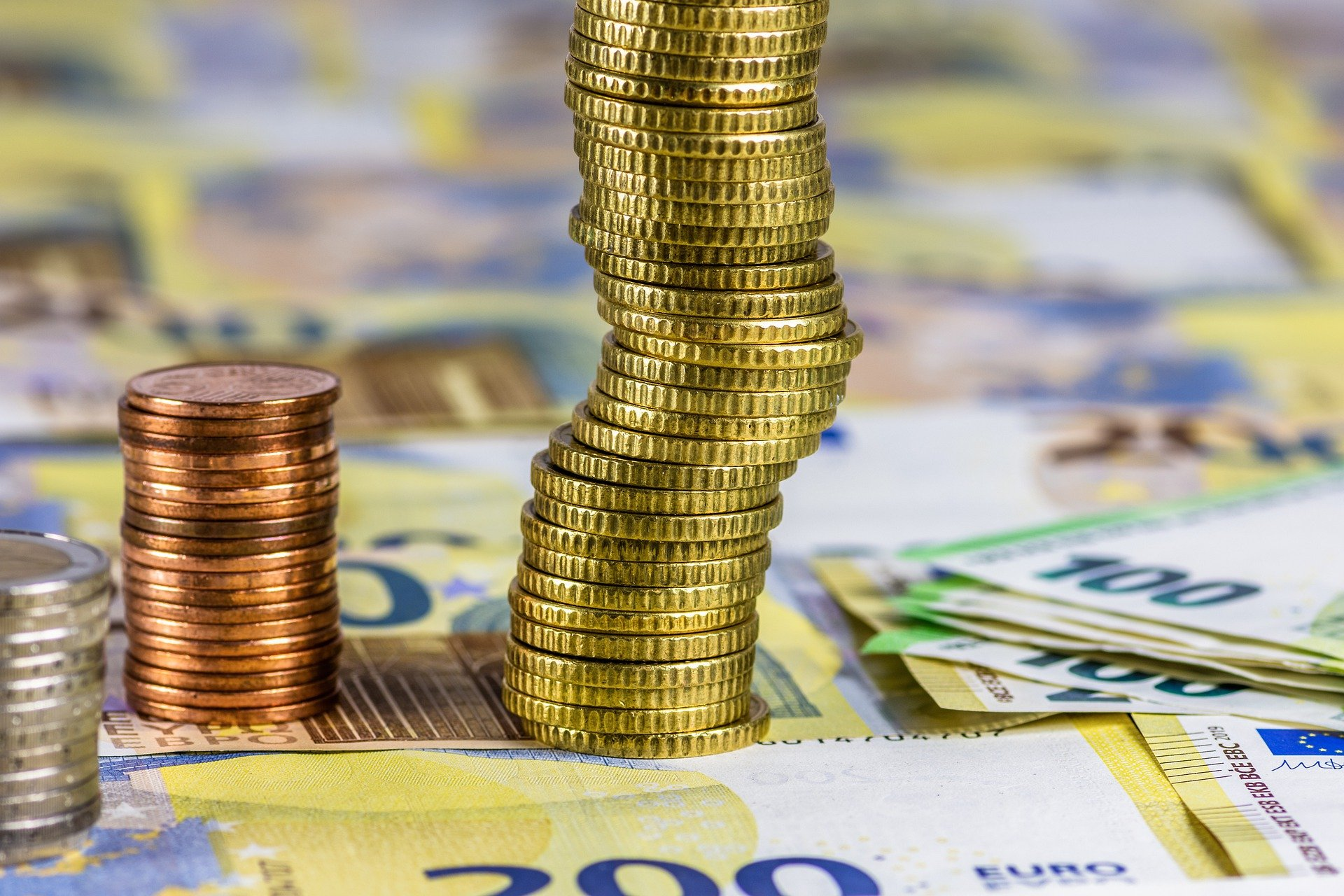 Vemos várias moedas empilhadas sobre algumas notas de dinheiro em uma superfície (imagem ilustrativa). Texto: royalties de franquias.