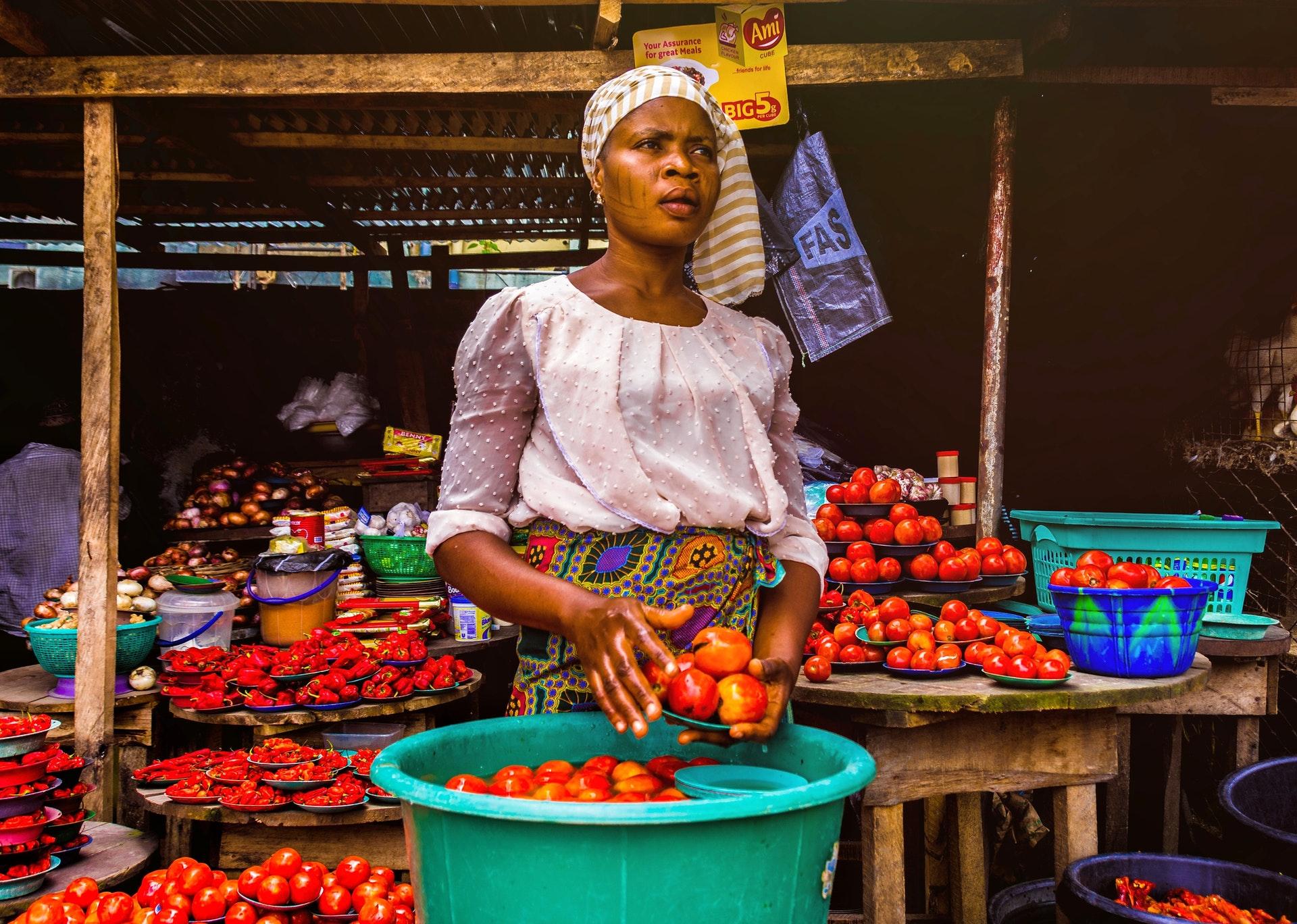 Vemos uma vendedora de frutas em uma rua (imagem ilustrativa). Texto: tipos de empresas.