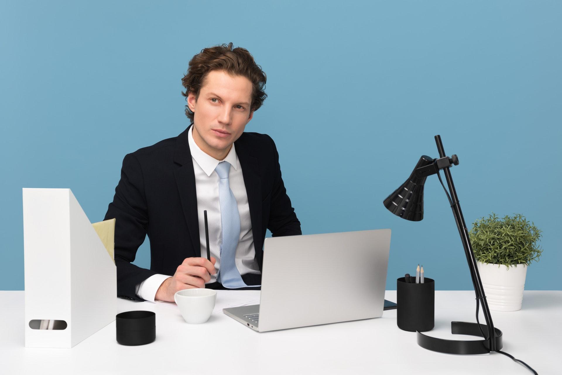 Vemos um empresário em uma mesa de escritório com um computador e uma luminária (imagem ilustrativa). Texto: tipos de empresas.