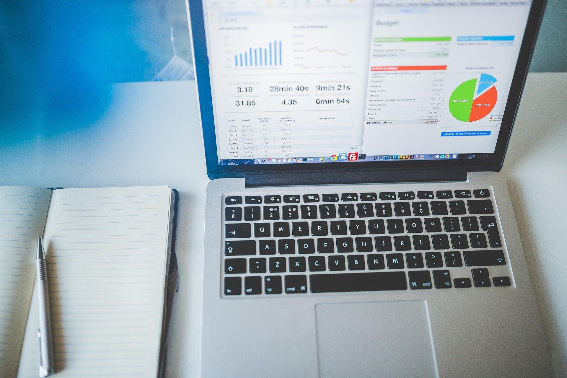Vemos sobre uma mesa um caderno, uma caneta e um computador, tendo gráficos em tela (imagem ilustrativa). Texto: tipos de negócios.