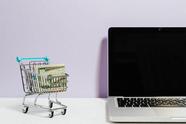 Imagem de um carrinho de comprar em miniatura ao lado de um computador. Imagem ilustrativa texto como abrir um ecommerce.