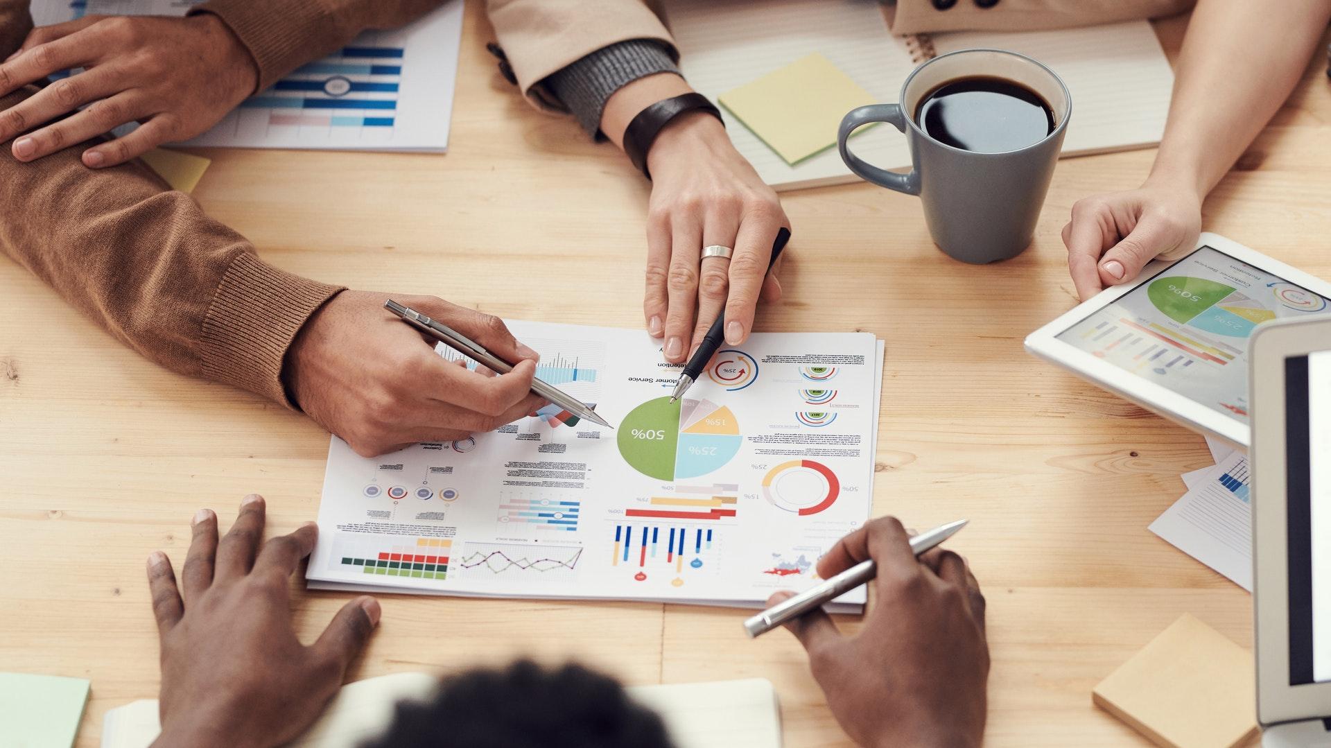 Vemos algumas pessoas em reunião; todos analisam um gráfico que está impresso sobre a mesa; há pessoas com computadores e tablets (imagem ilustrativa). Texto: como começar um pequeno negócio.