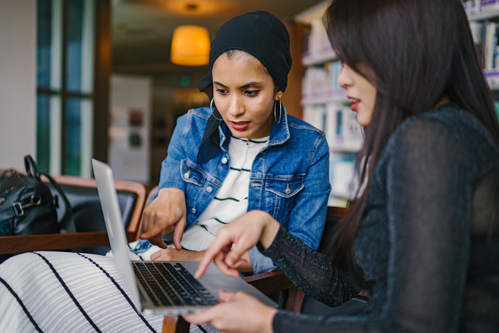 Vemos duas mulheres conversando enquanto analisam juntas, algo na tela de um computador (imagem ilustrativa). Texto: como começar um pequeno negócio.