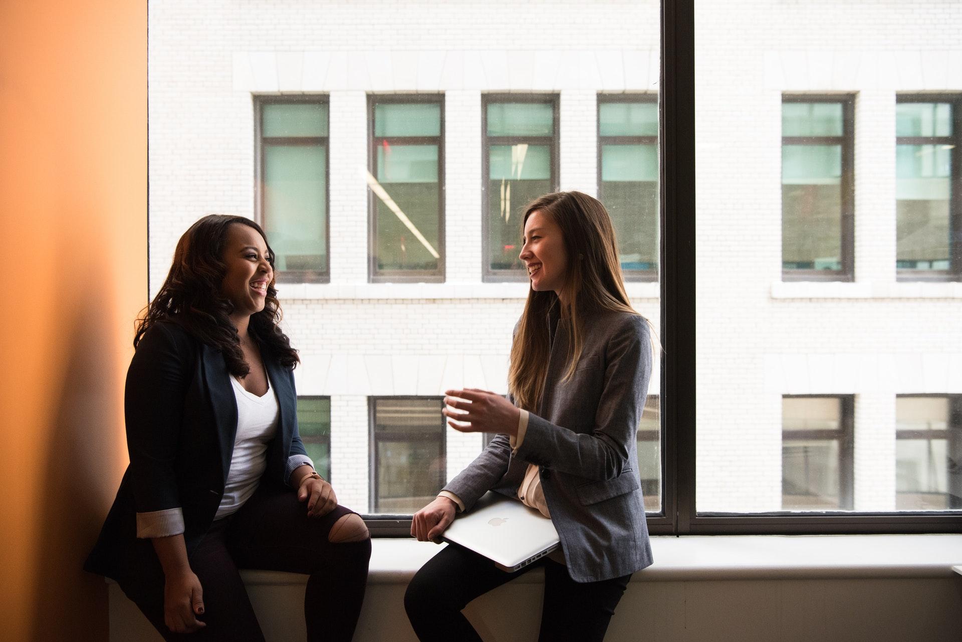 Vemos duas mulheres conversando; uma grande janela ao fundo, no que parece ser a sede de uma empresa (imagem ilustrativa). Texto: como começar um pequeno negócio.