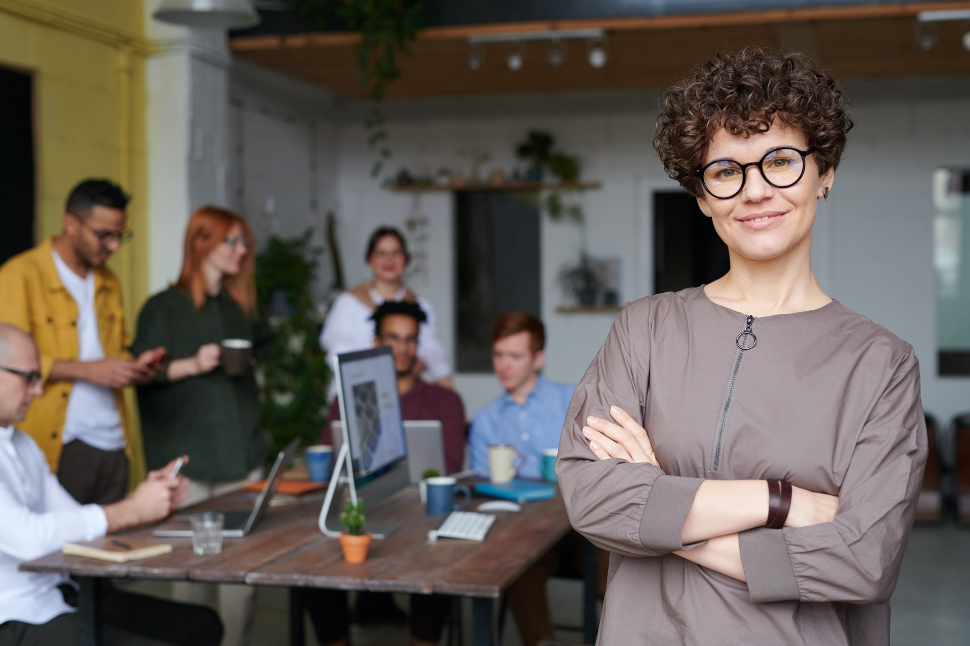 Imagem de uma mulher com um grupo de pessoas ao fundo em um pequeno negócio. Imagem ilustrativa texto como começar um pequeno negócio.
