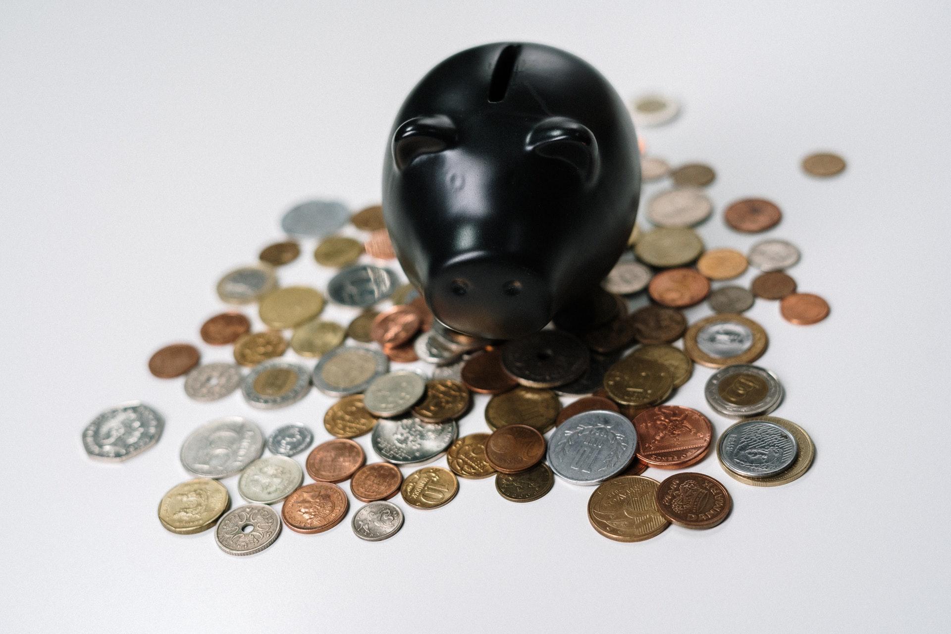 Vemos um cofrinho em formato de porco rodeado por moedas (imagem ilustrativa). Texto: empreendimento de baixo custo.