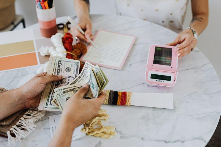 Imagem de uma pessoa contando dinheiro e outra usando uma calculadora e anotando em um caderno. Imagem ilustrativa texto empreendimentos de baixo custo.
