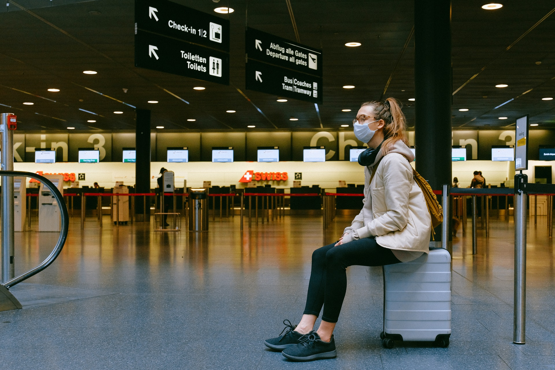 Vemos uma mulher sentada em cima da mala em um aeroporto (imagem ilustrativa). Texto: franquias baratas que valem a pena.