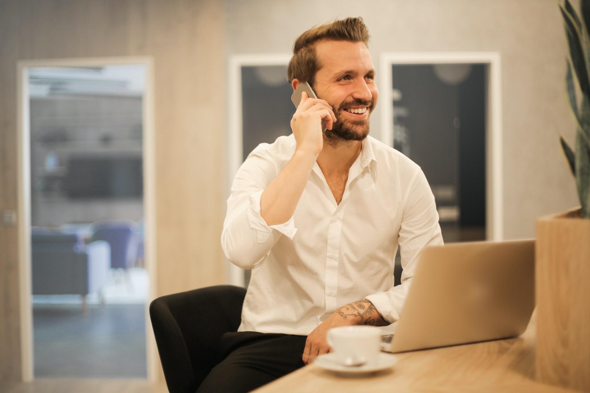 Vemos um homem feliz sentando em frente um computador enquanto fala ao telefone (imagem ilustrativa). Texto: franquias com faturamento alto.