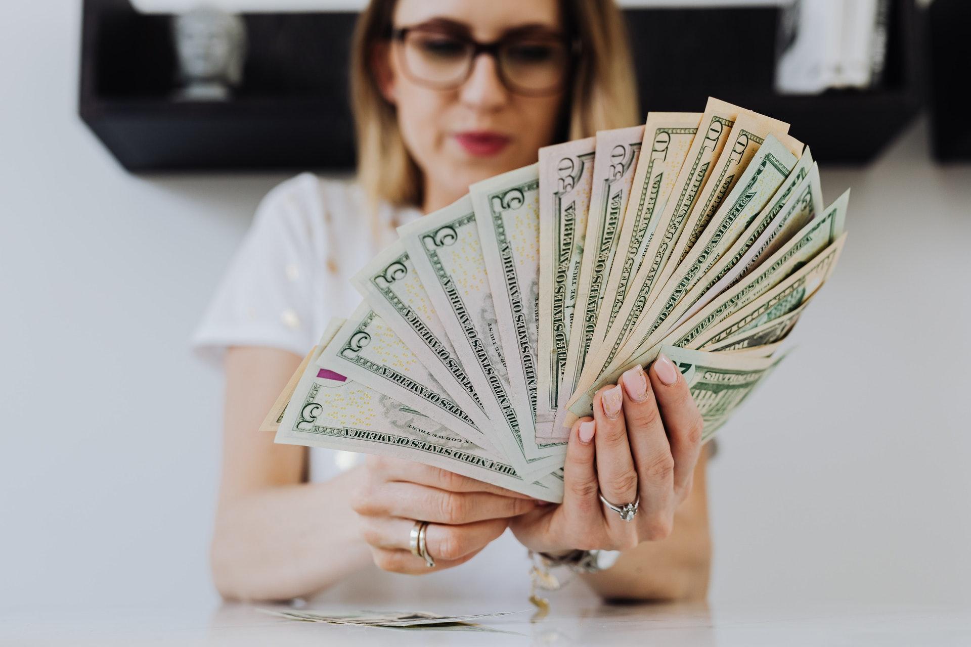 Imagem de uma mulher com a mão cheia de dólares. Imagem ilustrativa texto franquias com faturamento alto.