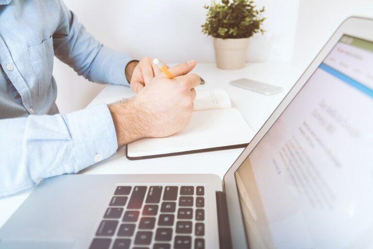 Imagem de duas mãos sobre a mesa perto de um computador. Imagem ilustrativa texto mini franquias.