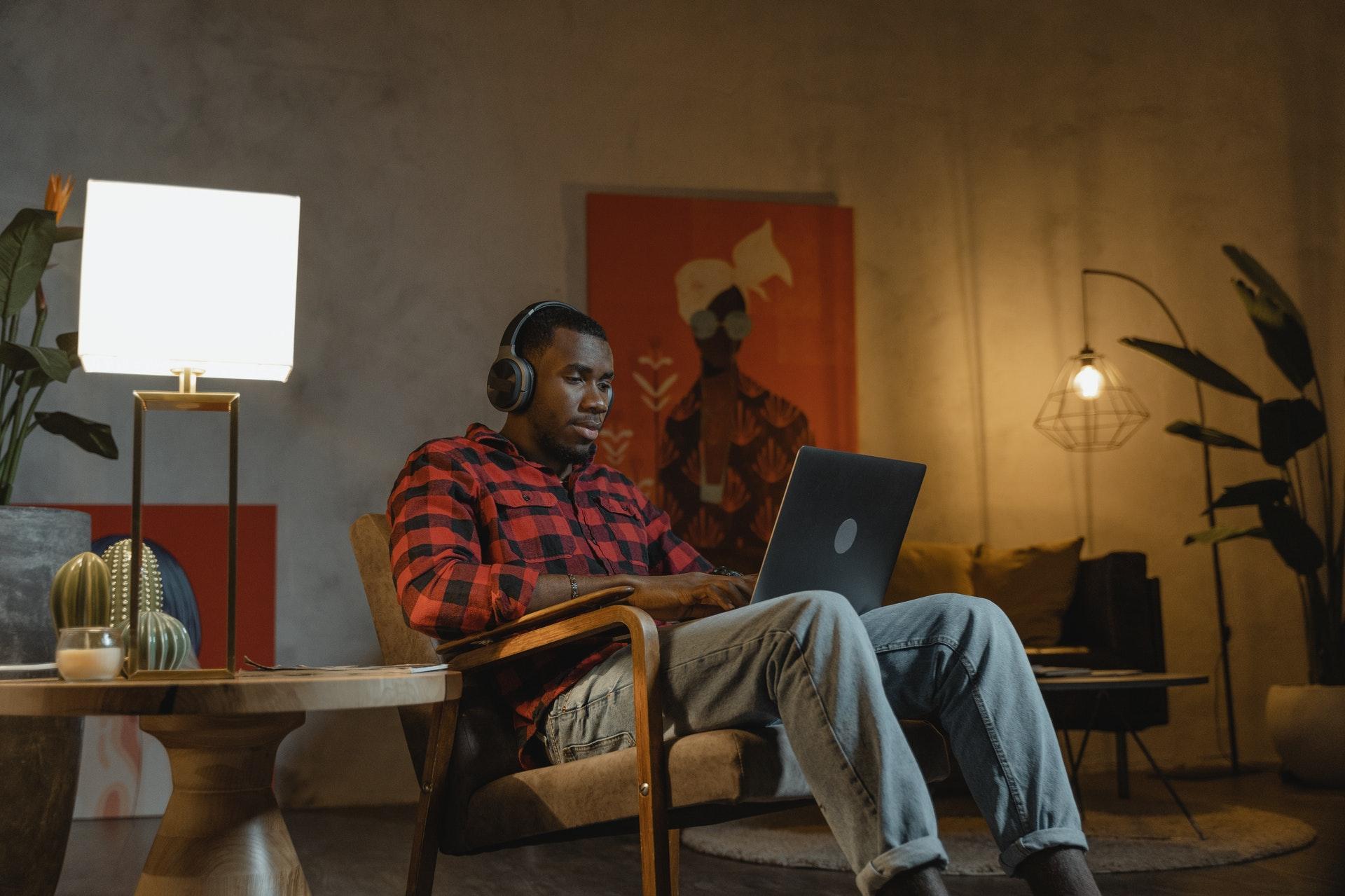 Vemos um homem trabalhando em seu computador no sofá de sua casa (imagem ilustrativa). Texto: negócios home office.