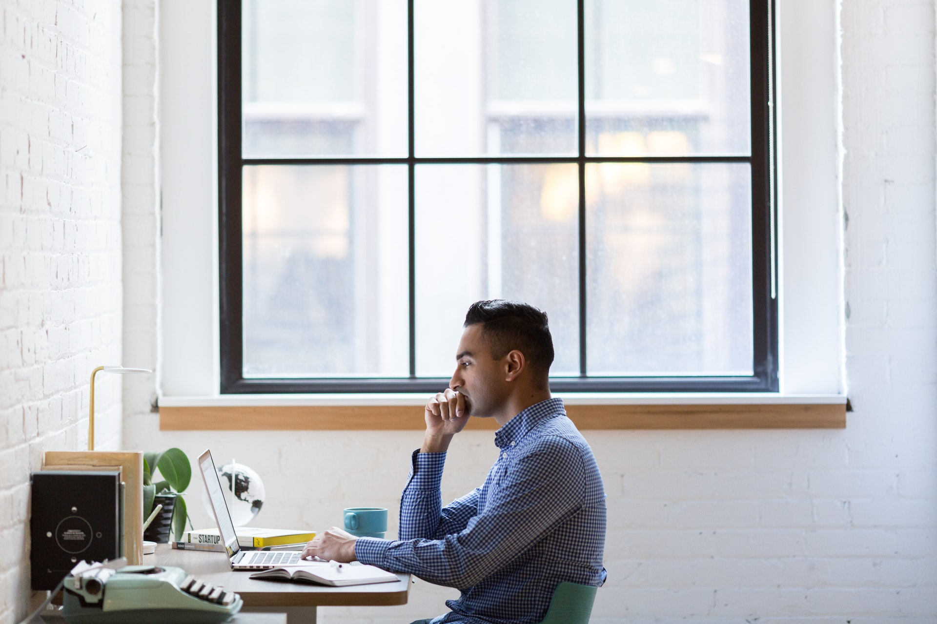 Imagem de um homem em casa trabalhando no computador na sala com uma grande janela ao fundo. Imagem ilustrativa texto negócios home office.