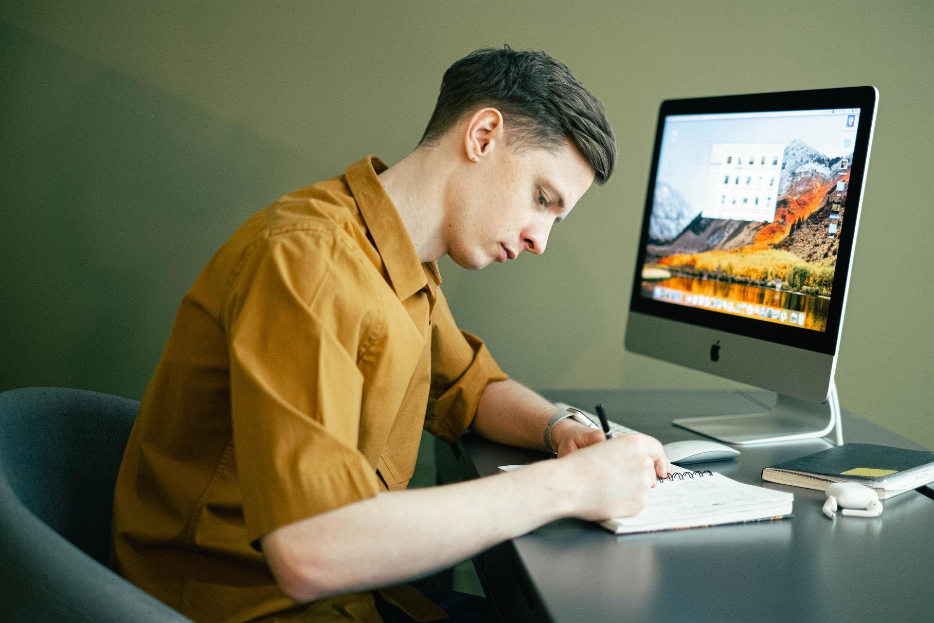 Vemos um homem anotando algo em um caderno; ele está à mesa, com um computador ao fundo (imagem ilustrativa). Texto: negócios home office.