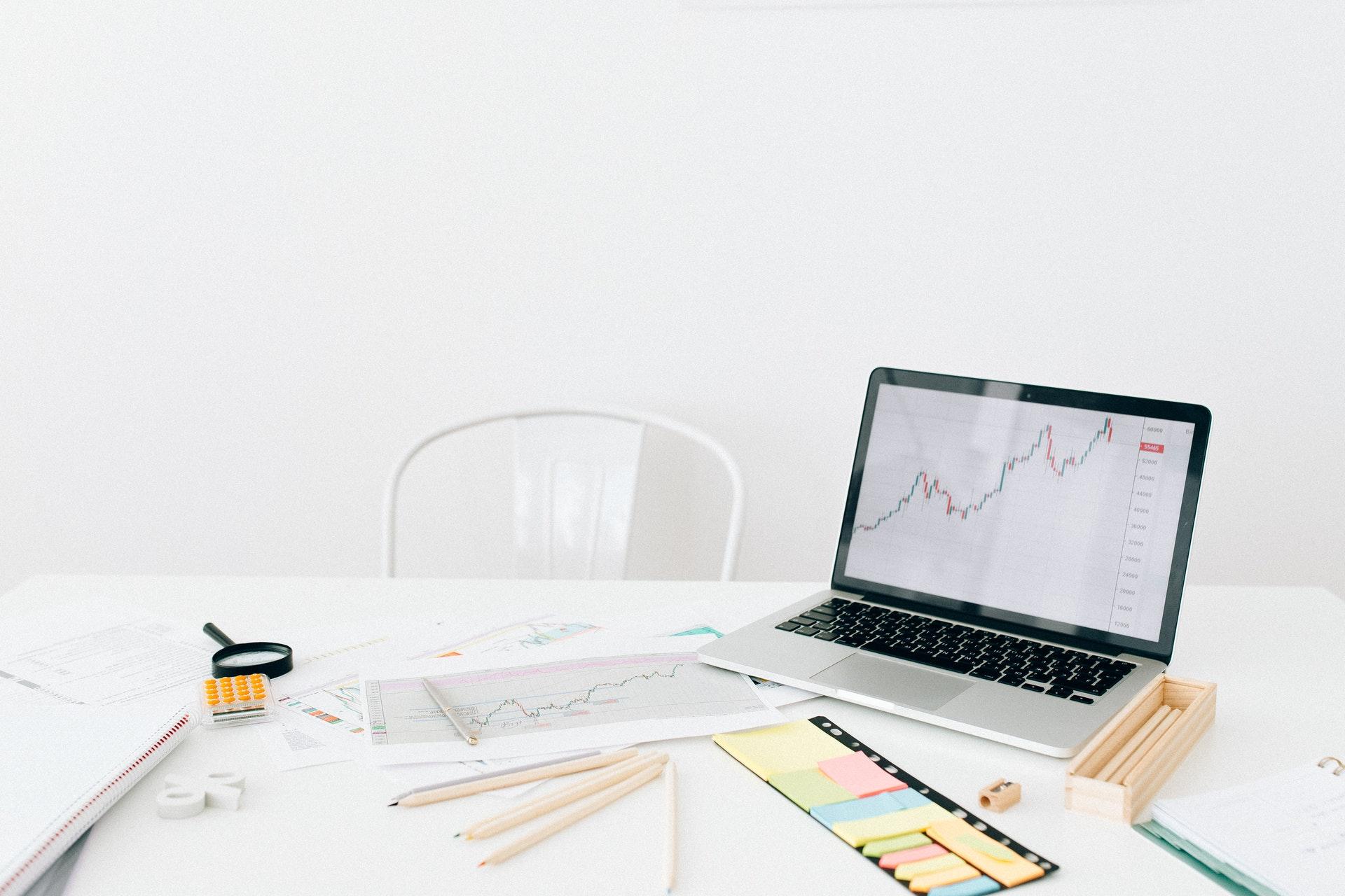 Imagem de uma mesa com um computador e vários papeis com gráficos. Imagem ilustrativa texto negócios mais promissores.