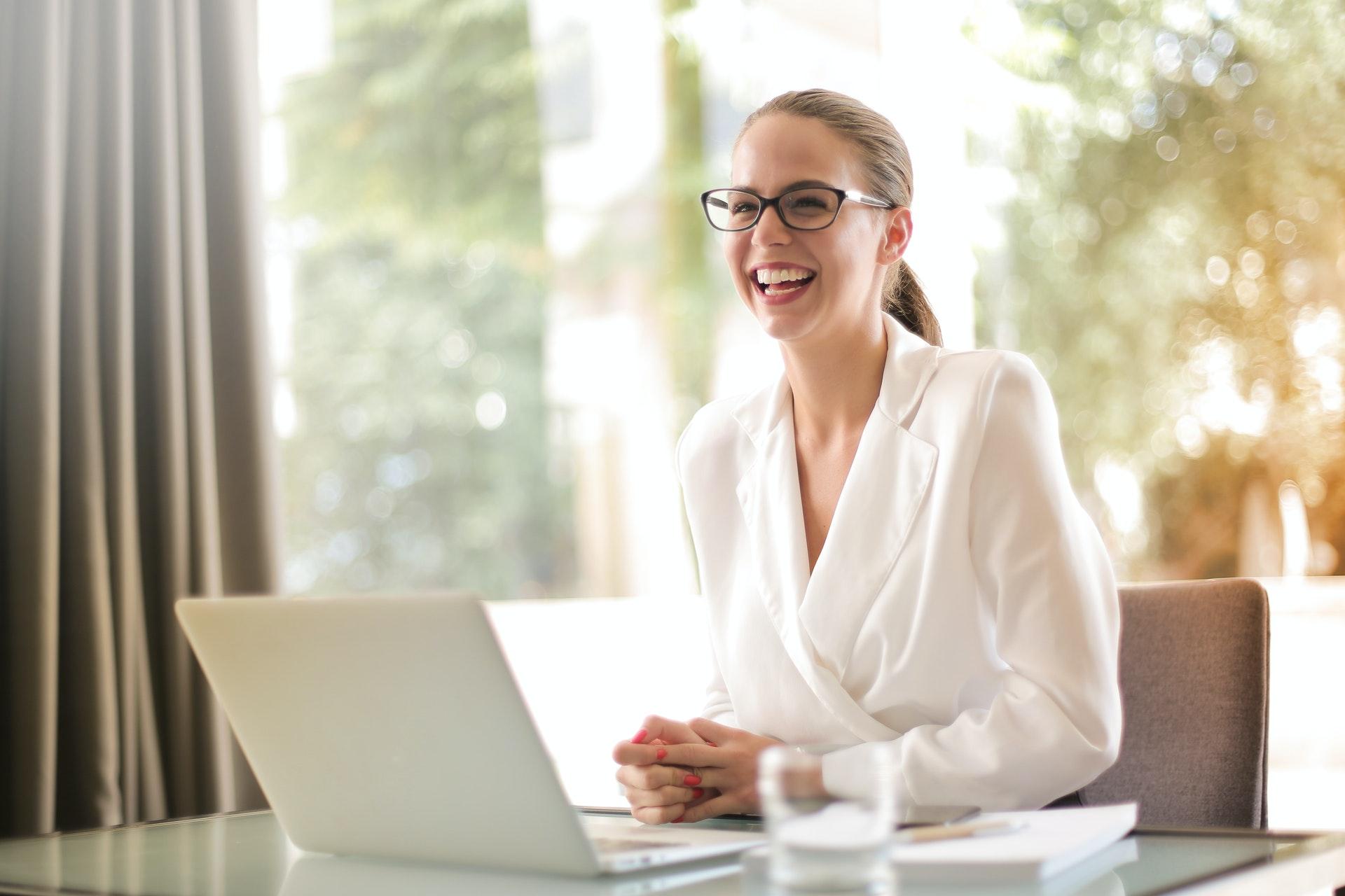 Vemos uma mulher sorrindo, sentada à mesa e um notebook; ela parece ocupar um cargo de peso em uma empresa (imagem ilustrativa). Texto: negócios rentáveis.