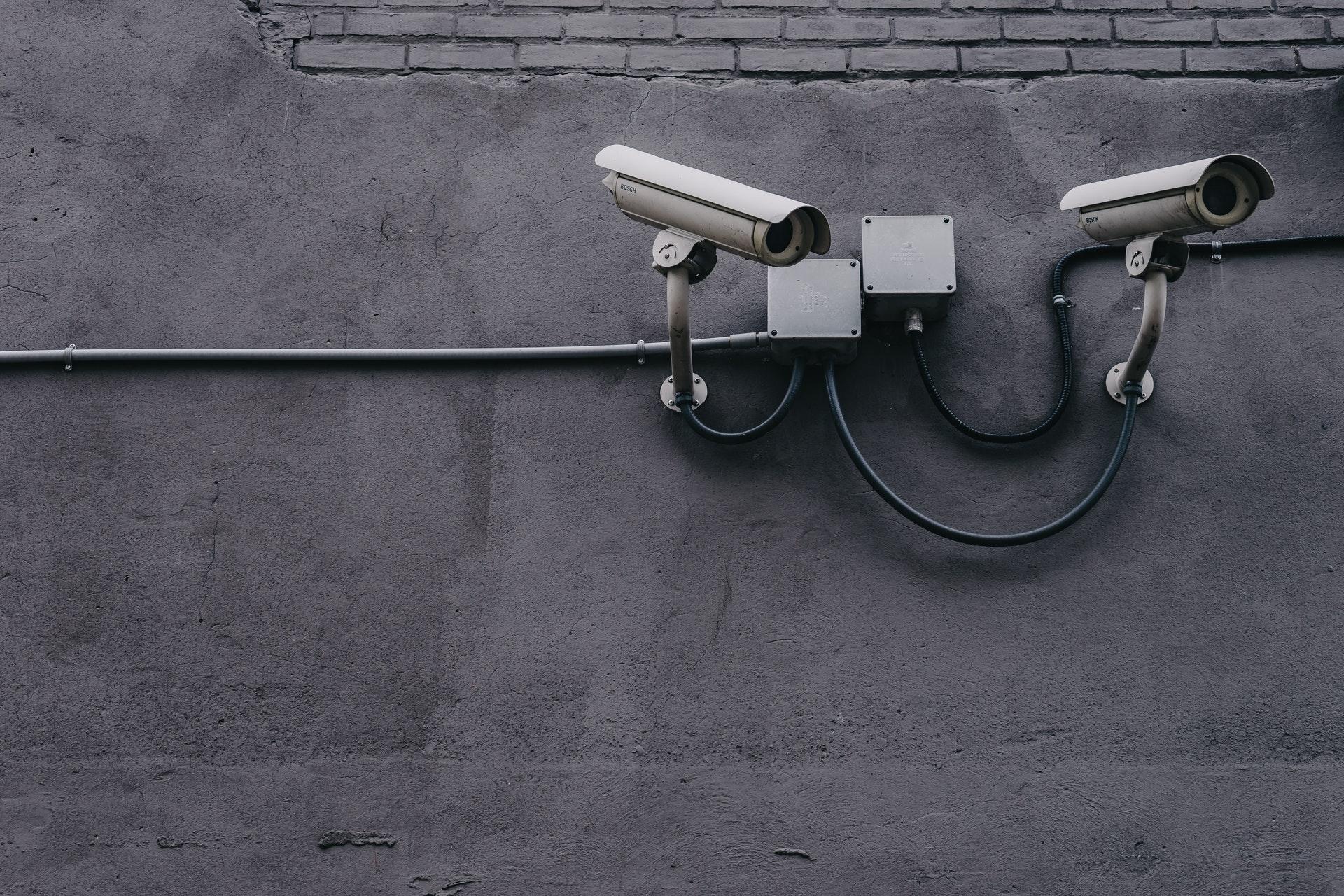 Vemos duas câmeras de segurança instaladas em um muro (imagem ilustrativa). Texto: negócios rentáveis.