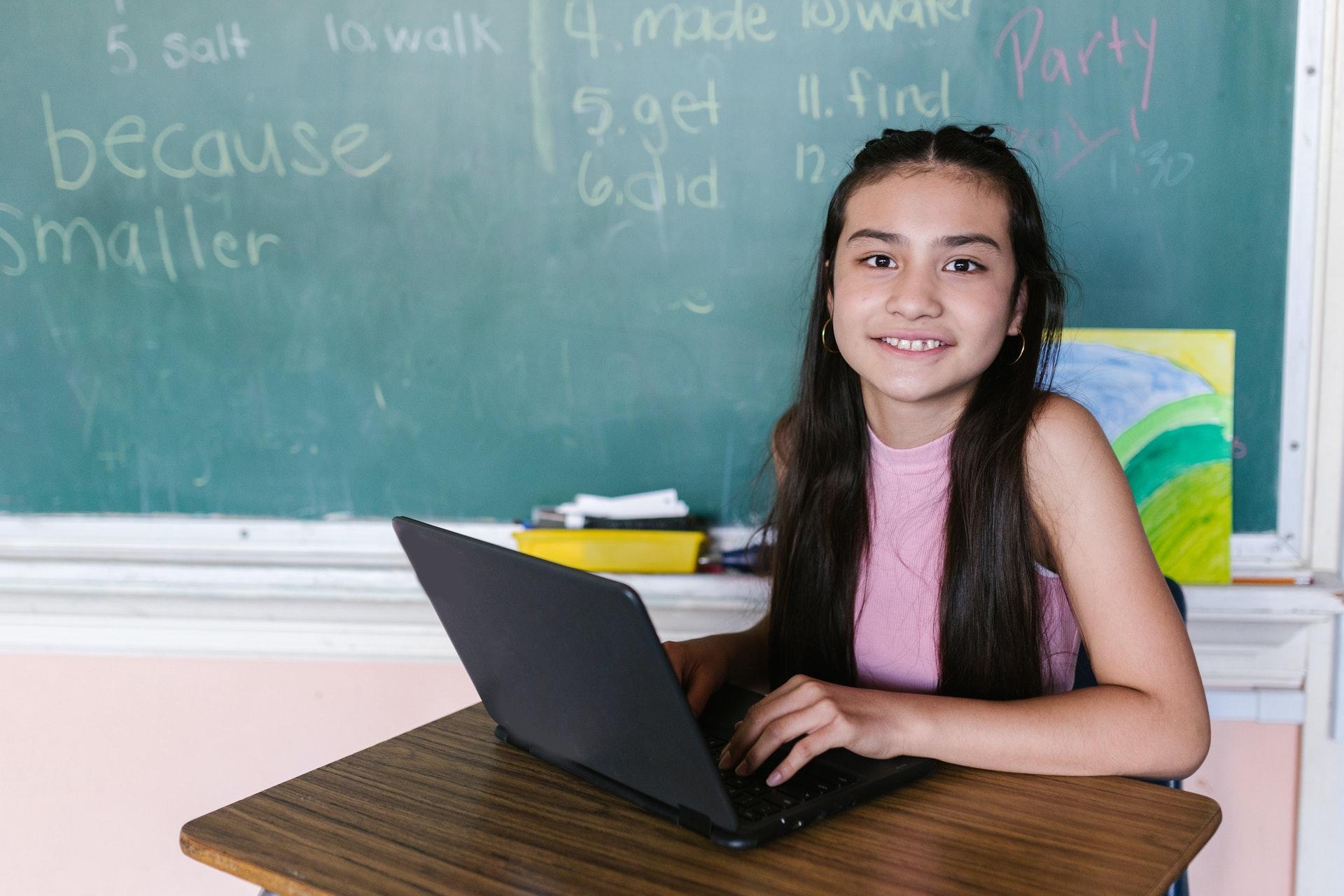 Vemos uma criança em uma sala de aula; ela tem um computador à mesa (imagem ilustrativa).