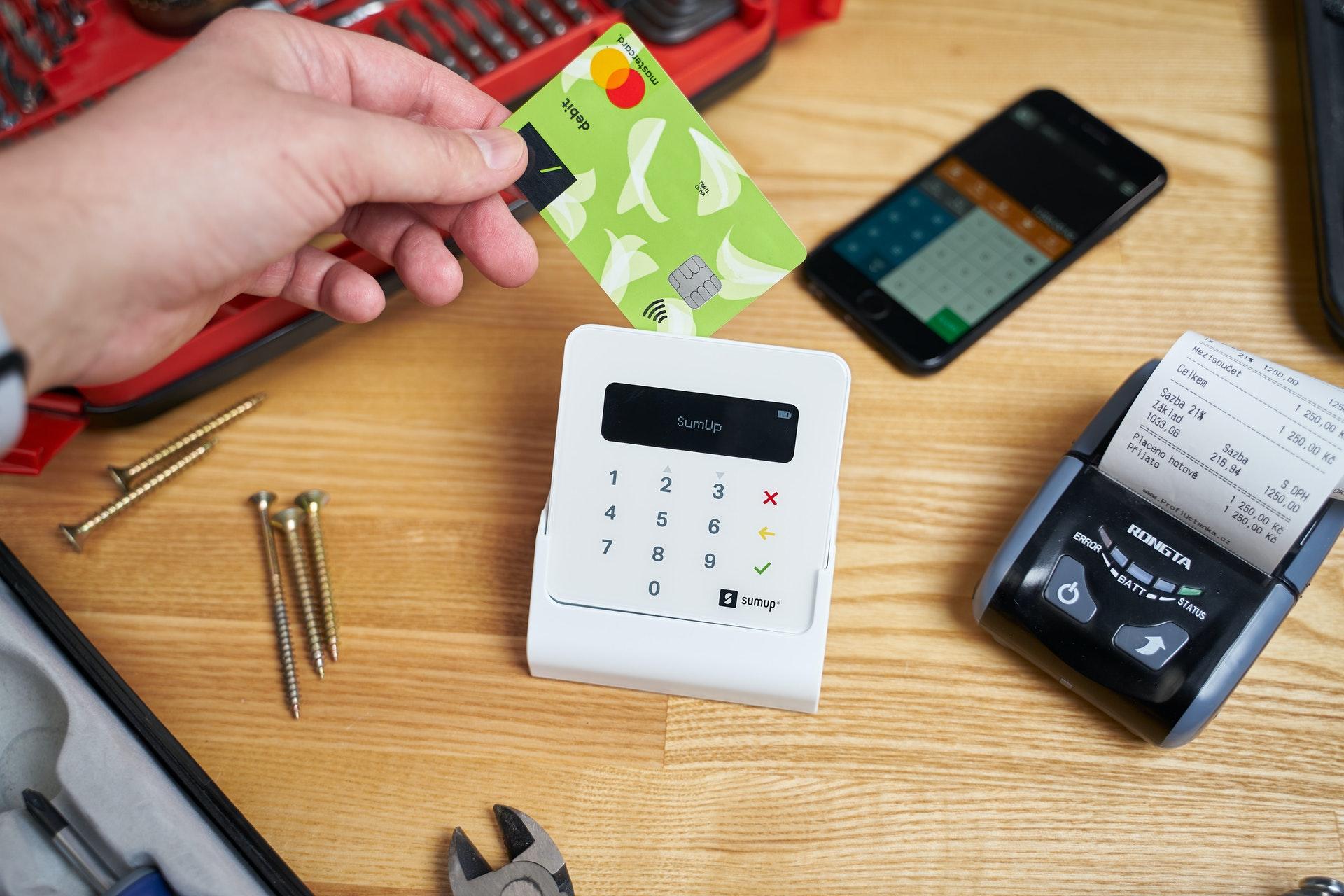 Vemos uma máquina de cartão branca em uma mesa; alguém está prestes a usá-la (imagem ilustrativa).