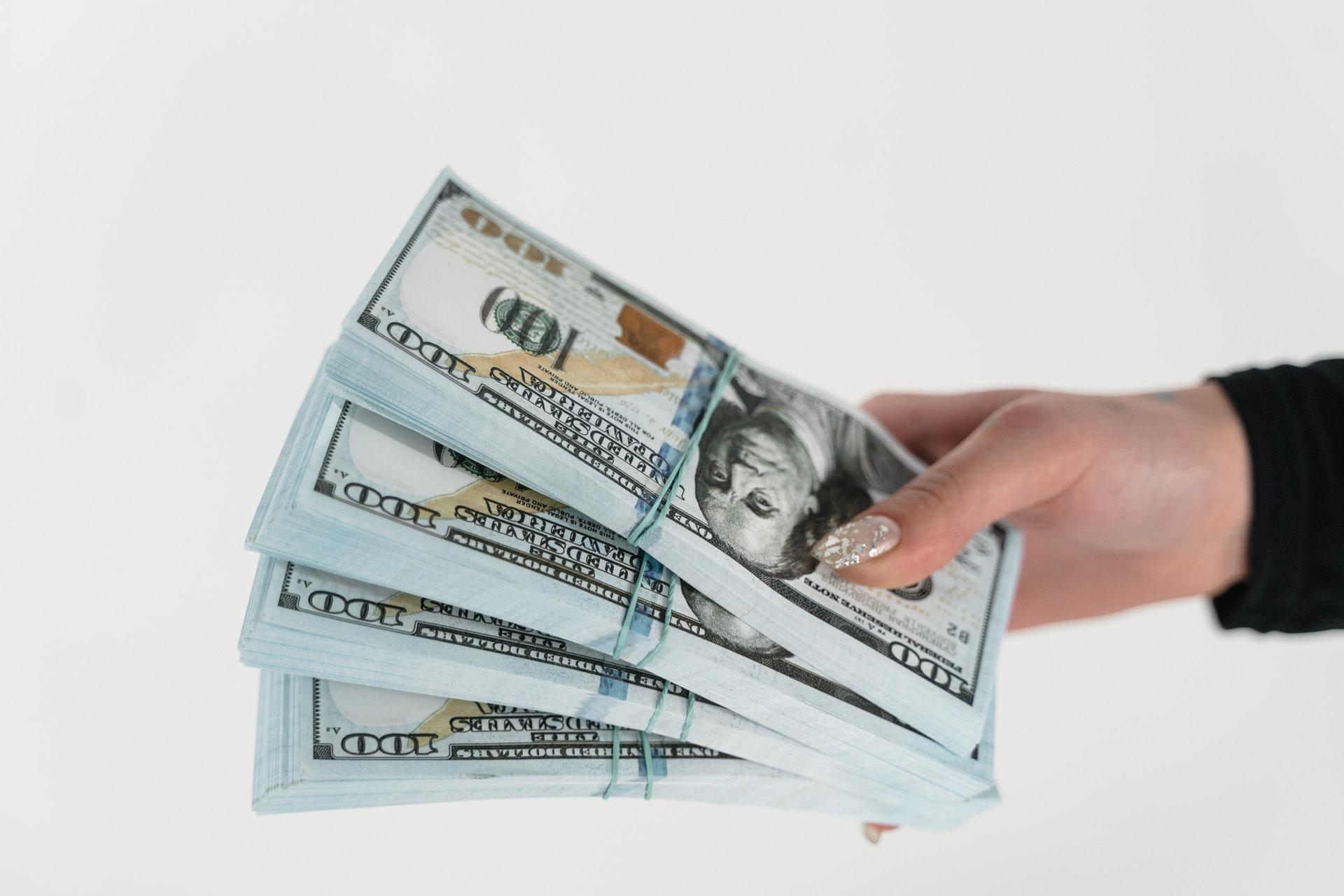 Imagem de quatro blocos de dólar na mão de uma pessoa. Imagem ilustrativa texto negócios rentáveis.