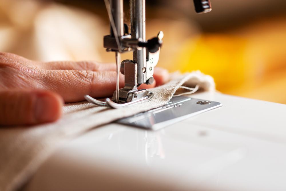 Close da mão de uma pessoa trabalhando em uma máquina de costura (imagem ilustrativa). Texto: o que é franquia.