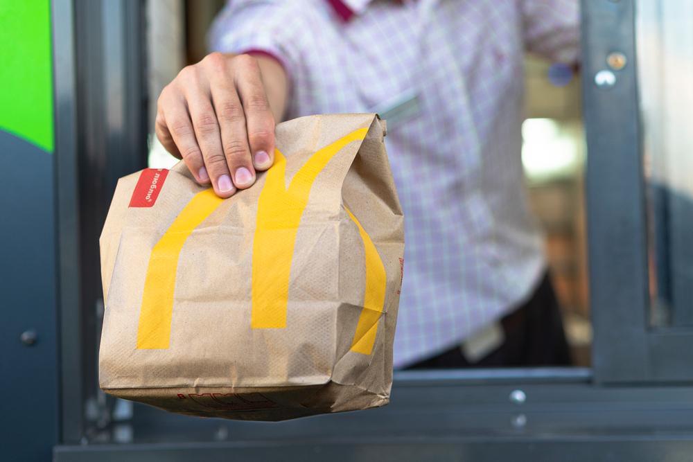 Vemos um atendente do MacDonald's entregando o lanche na janela do drive-thru (imagem ilustrativa). Texto: o que é franquia.