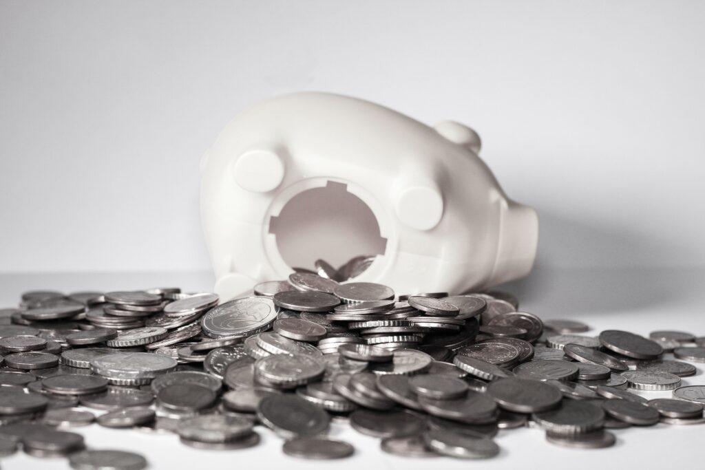 Vemos um cofre em formato de porco, aberto com algumas moedas espalhadas em uma superfície também branca (imagem ilustrativa). Texto: o que é franquia.