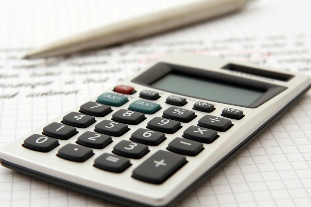 Vemos uma calculadora cinza, com uma caneta ao fundo sobre um papel com anotações (imagem ilustrativa). Texto: o que é franquia.