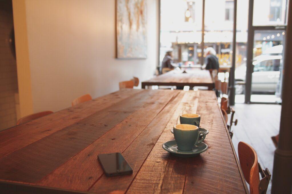Vemos uma mesa de madeira em um espaço bege e com vitrines. Na mesa, vemos duas xícaras azuis e um celular. Ao fundo, temos dois clientes em imagem desfocada (imagem ilustrativa).