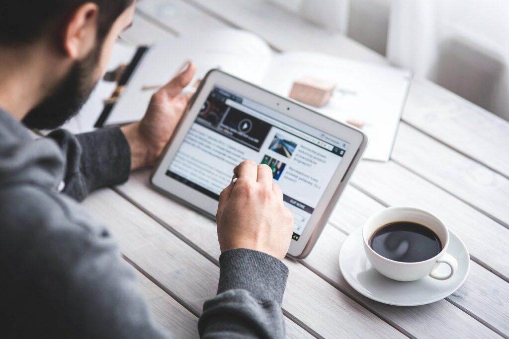 Vemos um homem de roupa cinza utilizando um tablet branco, com uma xícara de café ao lado e uma revista ao fundo. Vemos também uma mesa branca.