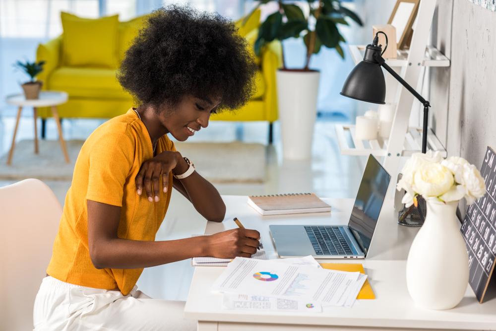 Vemos uma mulher negra usando blusa amarela e calça branca em um mesa com computador e papéis, enquanto realiza algumas anotações (imagem ilustrativa).