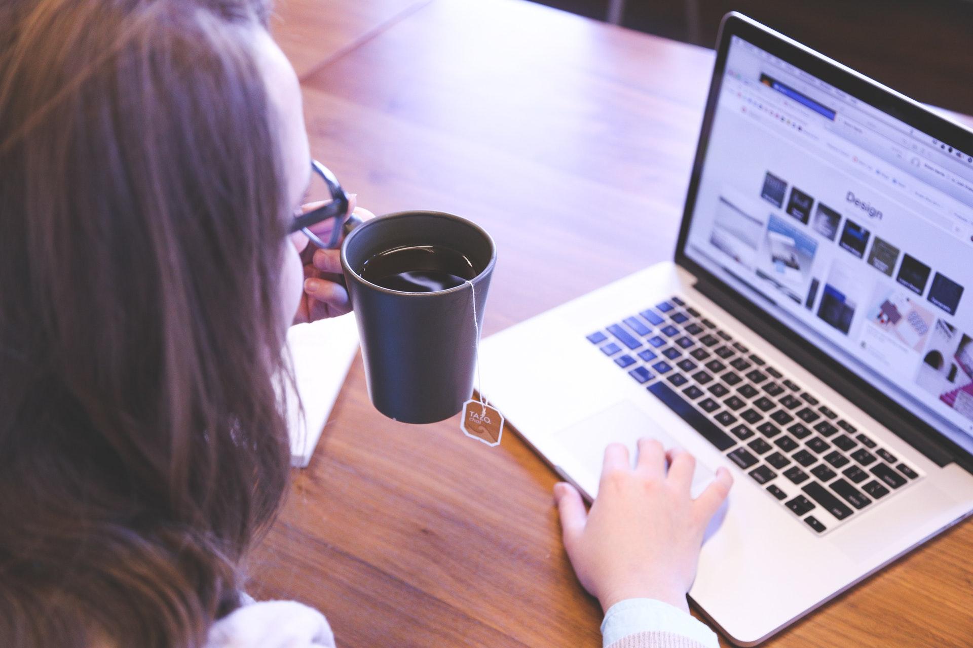 Vemos uma mulher tomando uma xícara de café enquanto utiliza o seu computador; aparentemente ela está na sala de estar de casa (imagem ilustrativa). Texto: o que é home based.