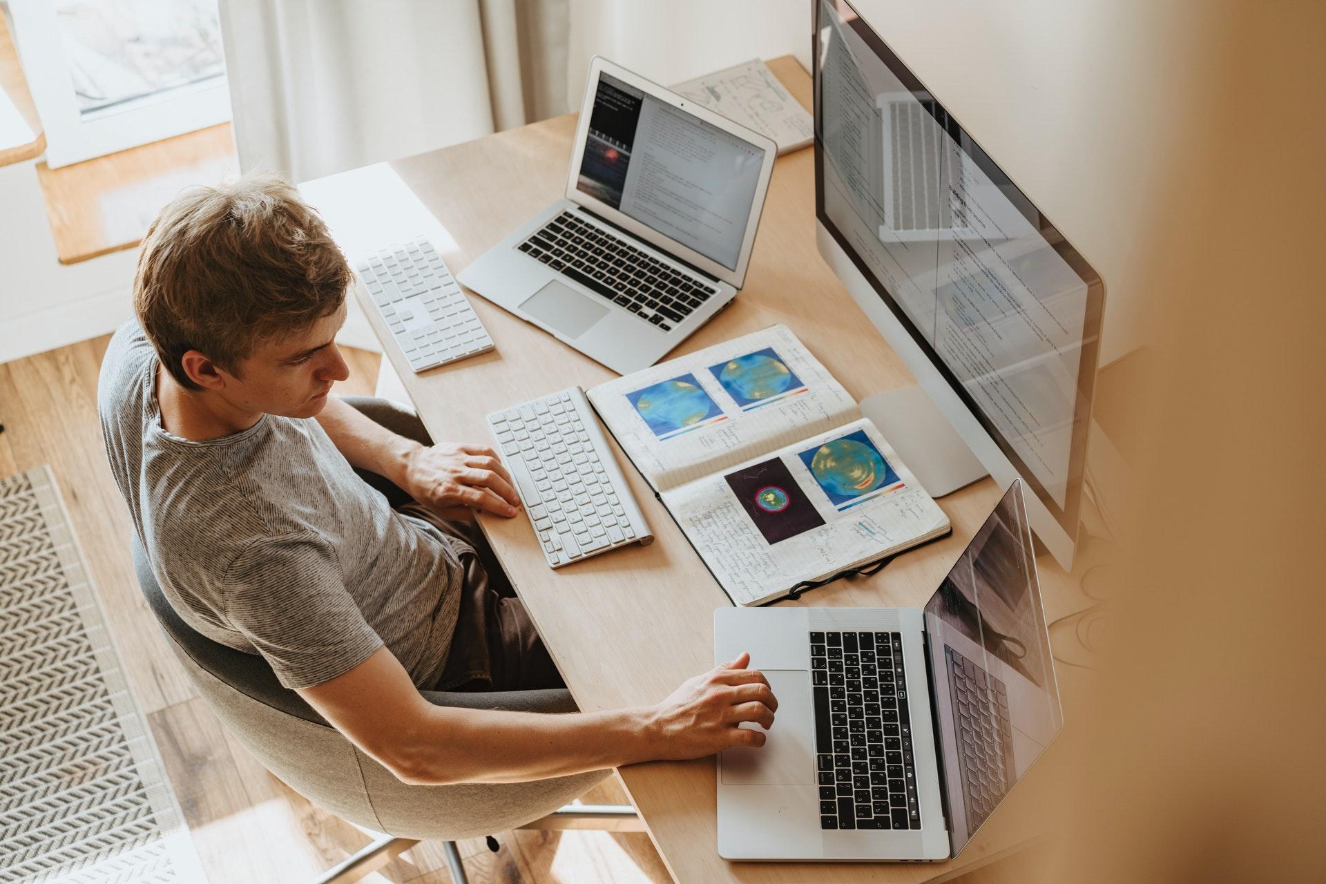 Imagem de um homem em uma mesa de escritório em casa com três telas de computador em cima da mesa. Imagem ilustrativa texto o que é home based.
