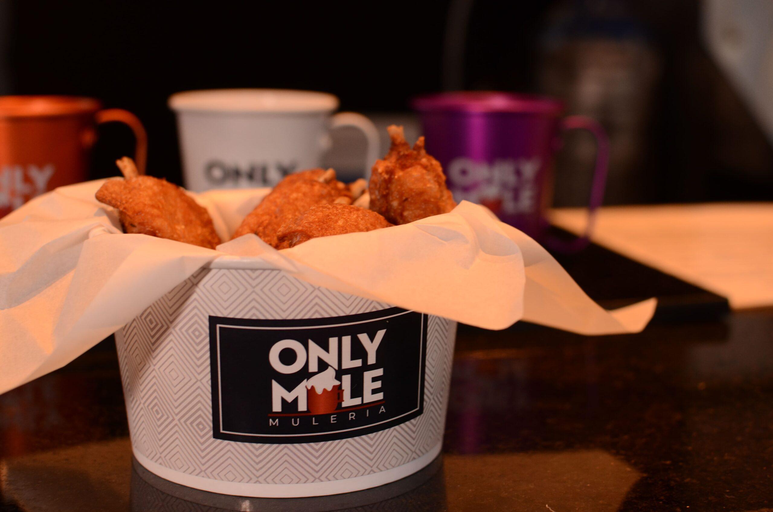 Imagem de um baldinho com a marca Only Mule cheio de aperitivos.