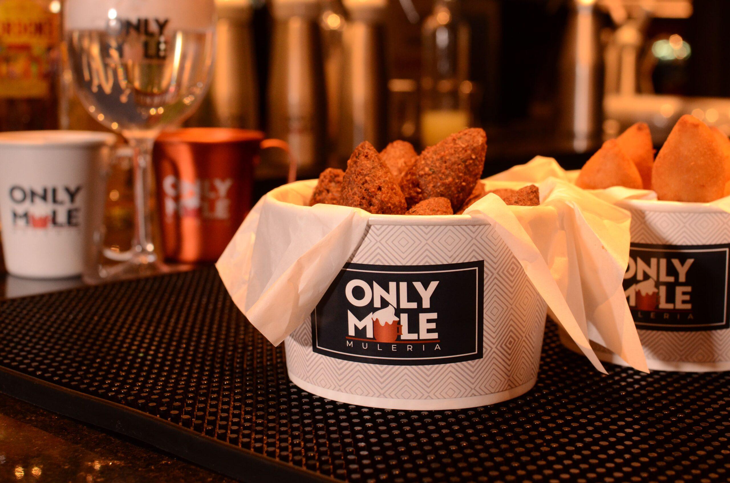 Vemos um balde com salgados (coxinha e kibe frito) com a logo da Only Mule e canecas ao fundo (imagem ilustrativa). Texto: franquia Only Mule.