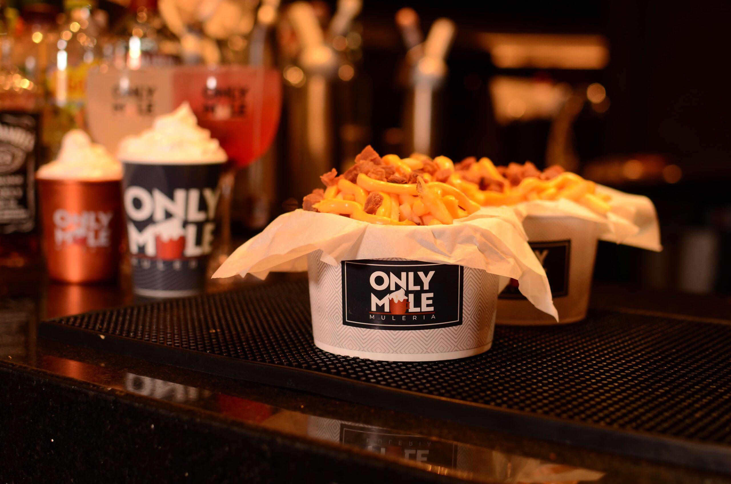 Imagem de uma porção de petiscos em um balde escrito Only Mule e uma caneca ao fundo escrito Only Mule e com espuma branca.