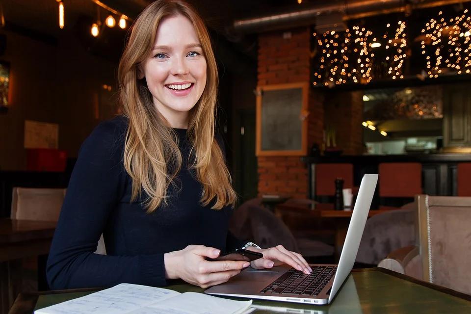 mulher sorrindo e usando o notebook imagem ilustrativa texto como abrir uma franquia de sucesso