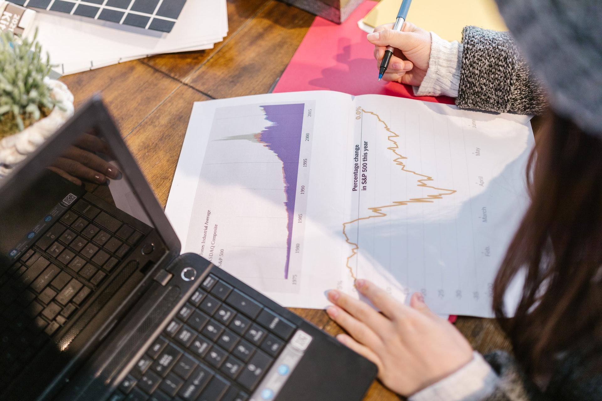 Vemos uma mulher olhando gráficos em uma folha impressa (imagem ilustrativa). Texto: como empreender do zero.