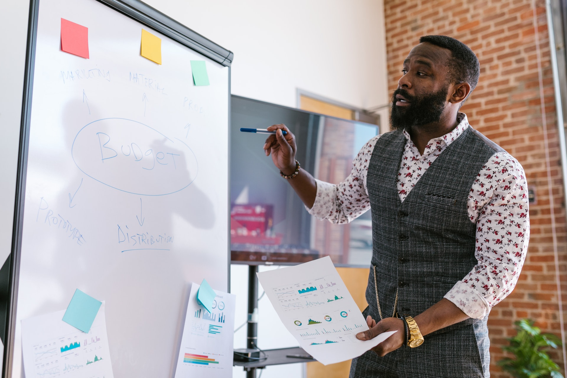 Vemos um homem explicando algo com a ajuda de um quadro; ele aparenta estar em um escritório (imagem ilustrativa). Texto: empreendedorismo na pandemia.