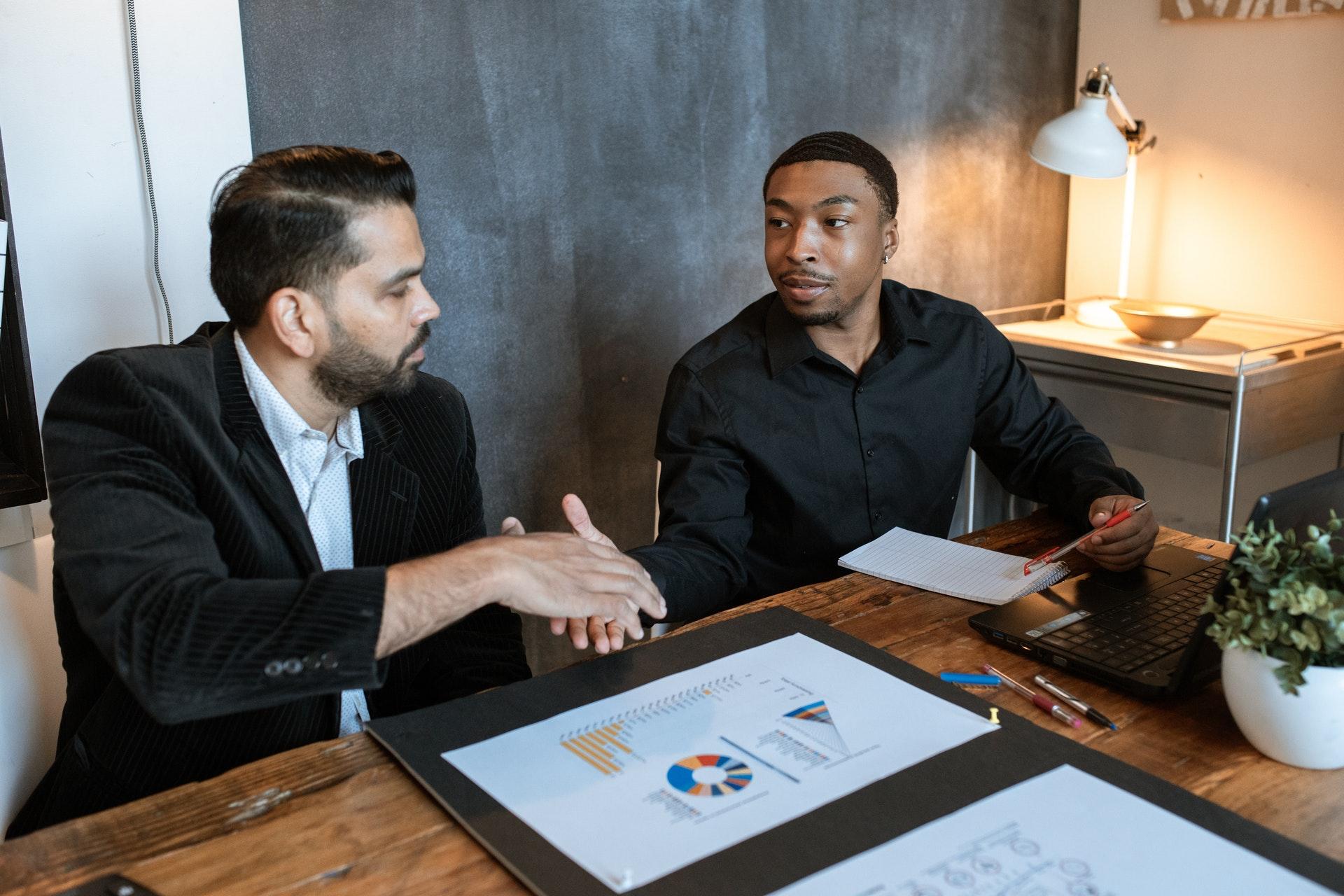 Vemos dois homens de negócio se cumprimentando em uma mesa de reunião (imagem ilustrativa). Texto: empreendedorismo na pandemia.