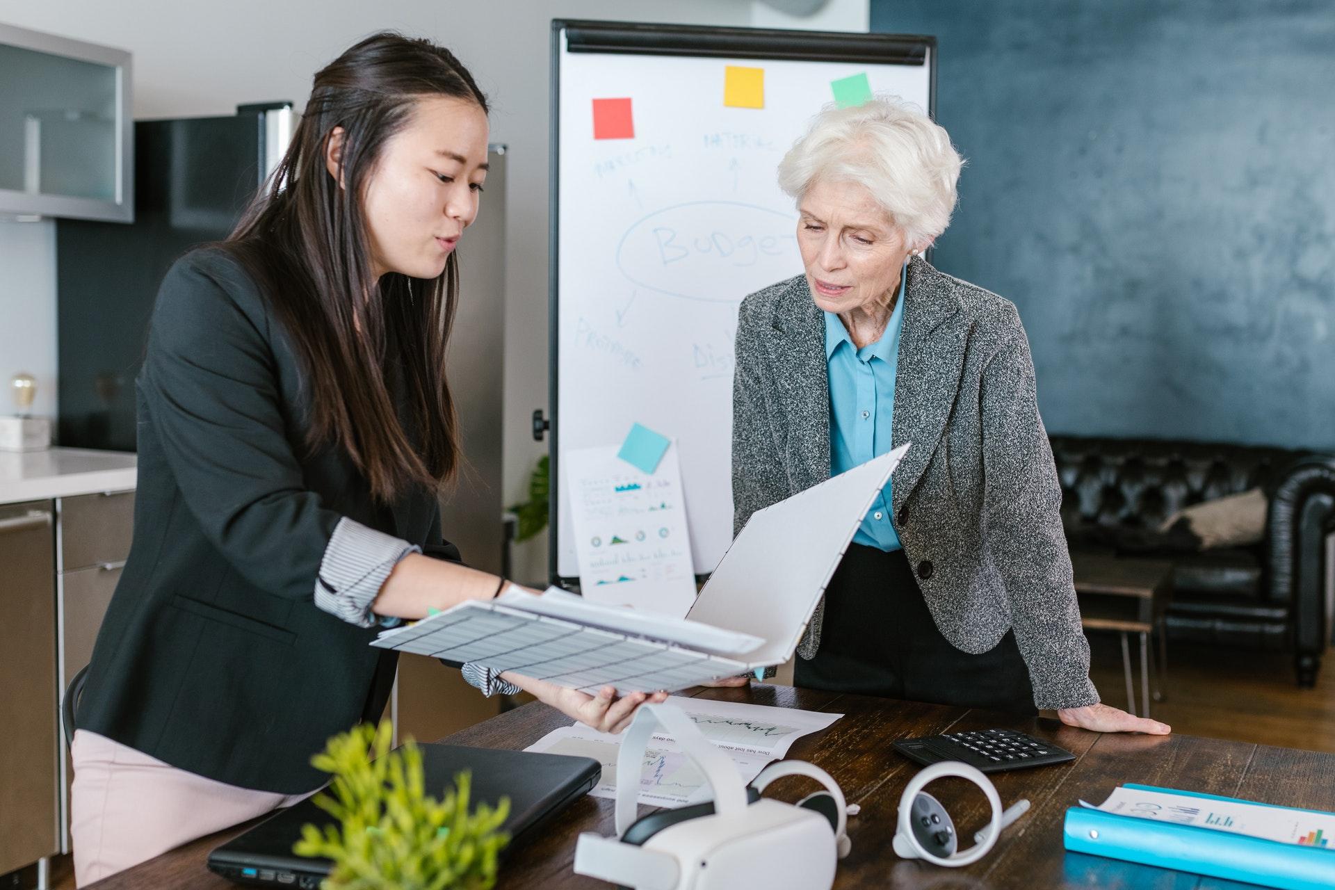 Vemos duas mulheres conversando; uma delas aponta para um documento em mão enquanto a outra o analisa (imagem ilustrativa).