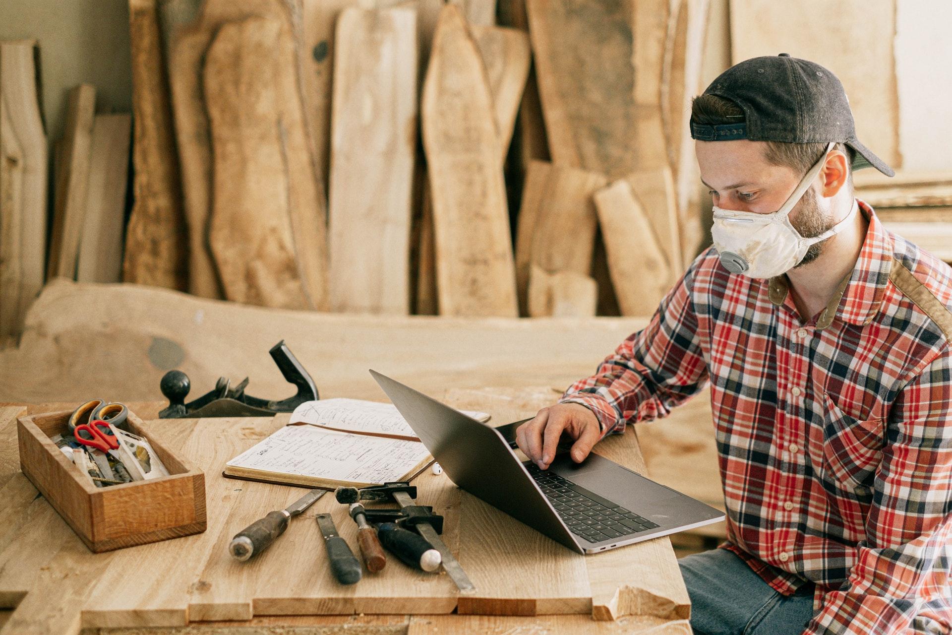 Imagem de um homem de mascara em uma serralheria olhando para um computador. Imagem ilustrativa texto empreendedorismo na pandemia.