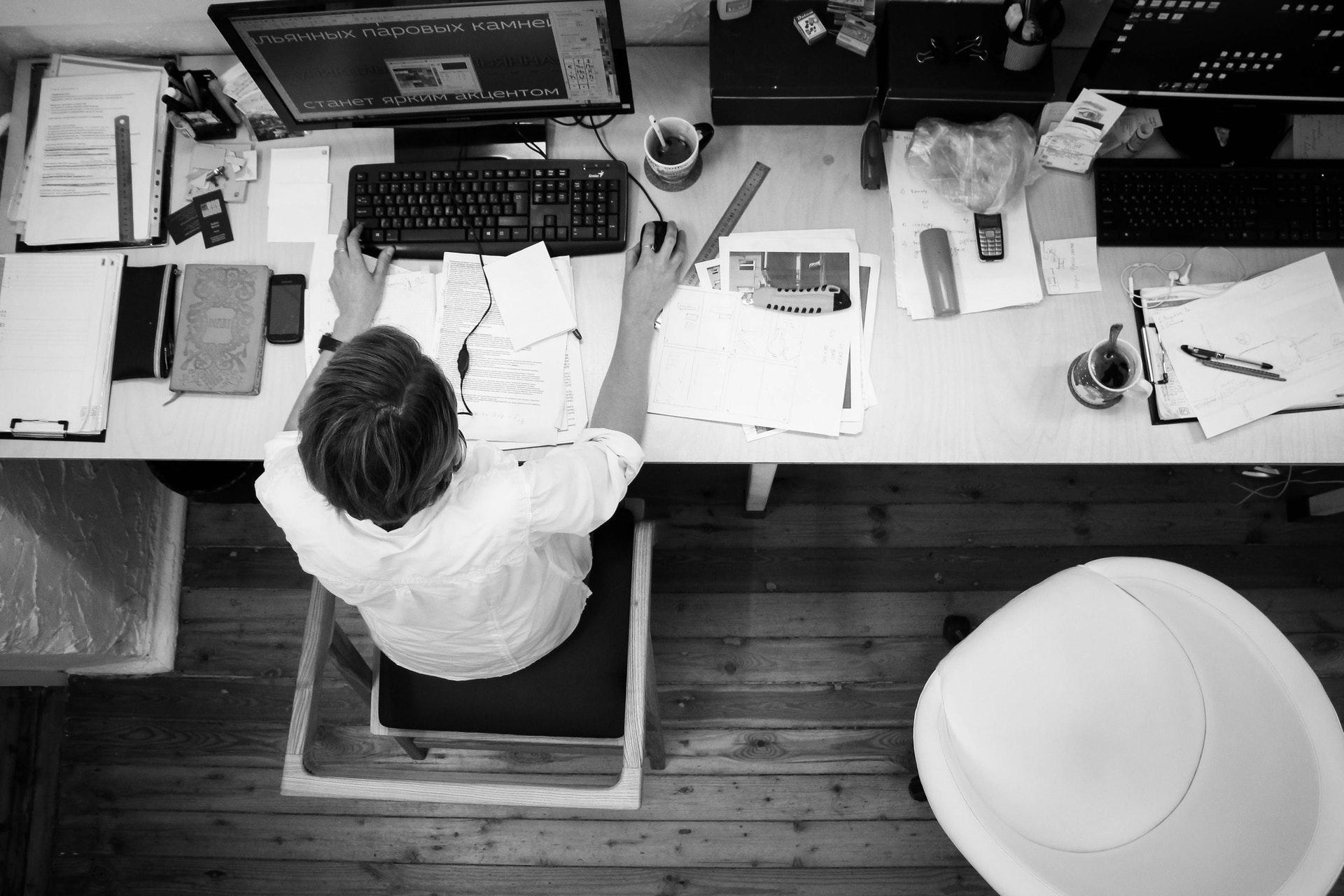 Vemos uma mulher trabalhando em uma mesa de escritório com diversos materiais espalhados (imagem ilustrativa). Texto: empreender ou investir.