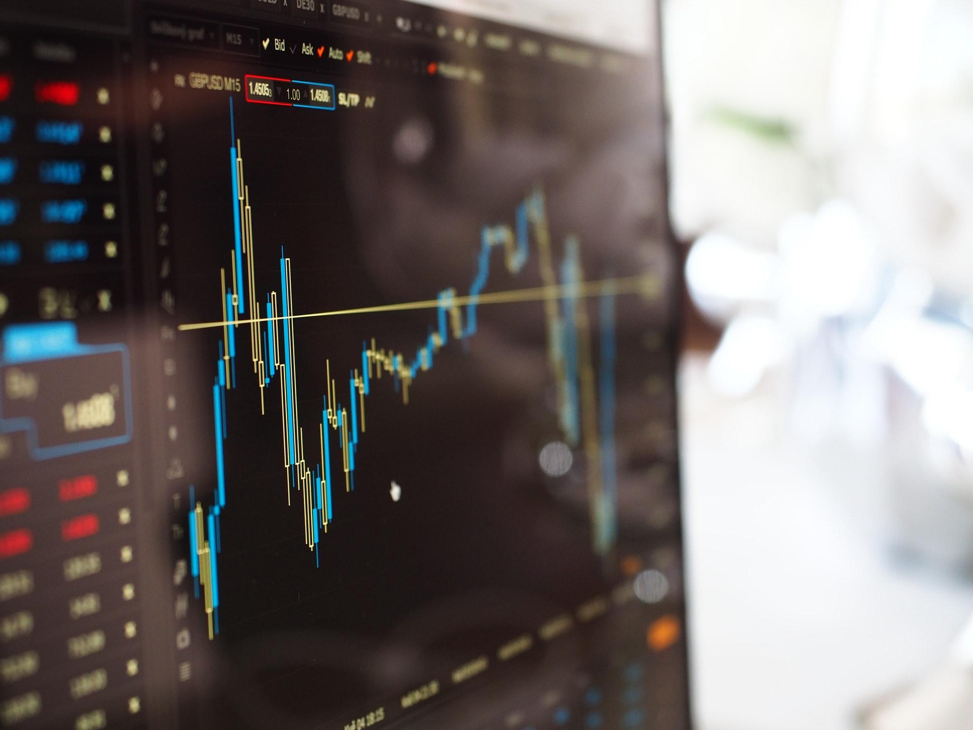 Vemos alguns gráficos do mercado de ações em tela (imagem ilustrativa). Texto: empreender ou investir.