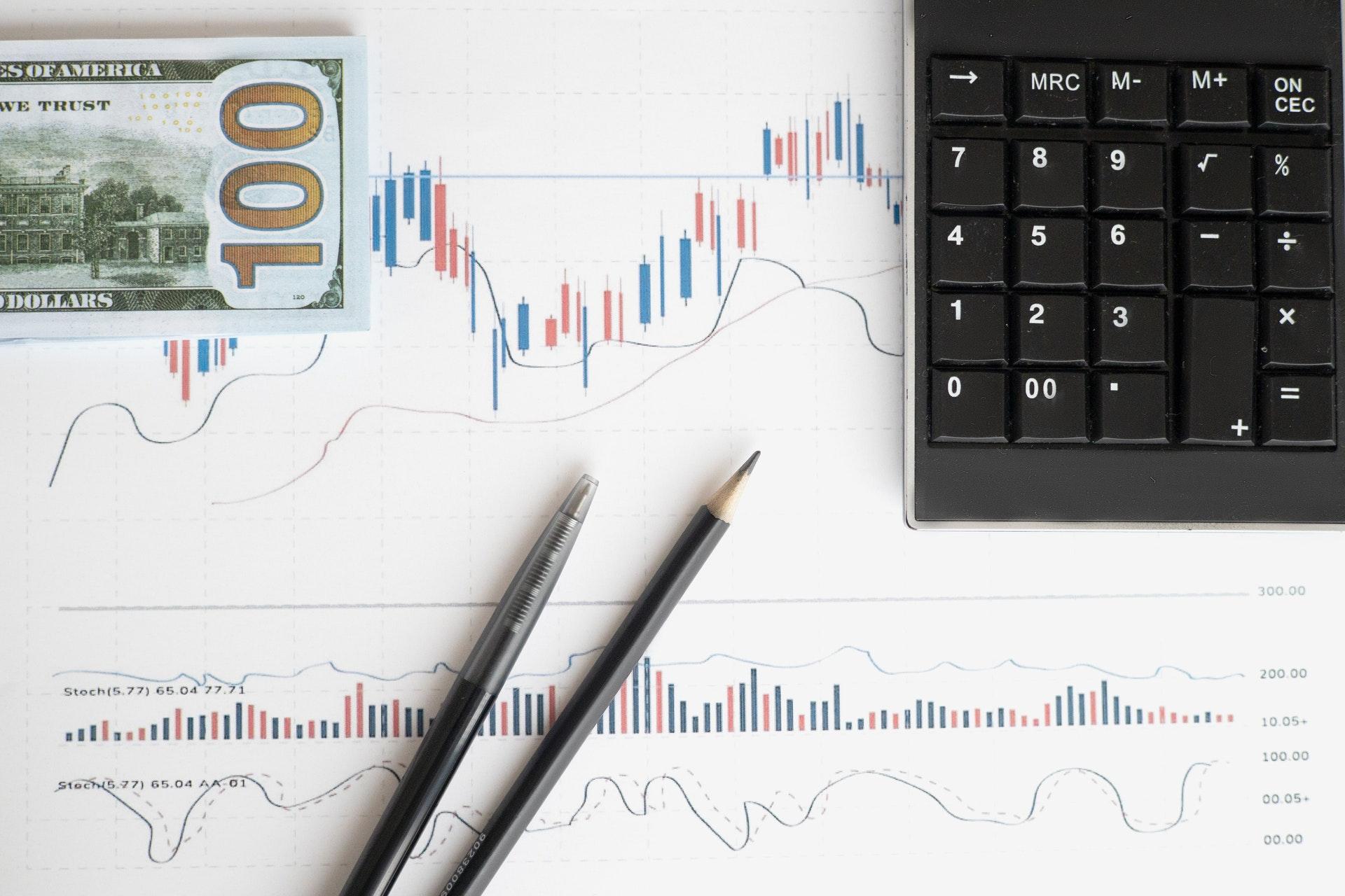 Vemos alguns gráficos impressos em papel; sobre o material temos uma calculadora, uma nota de dinheiro, caneta, lápis e parte de um teclado numérico (imagem ilustrativa). Texto: empreender ou investir.