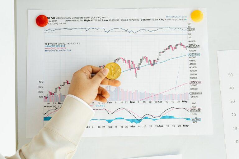 Imagem de uma mão segurando uma moeda e uma folha com gráficos de ações no fundo. Imagem ilustrativa texto empreender ou investir.
