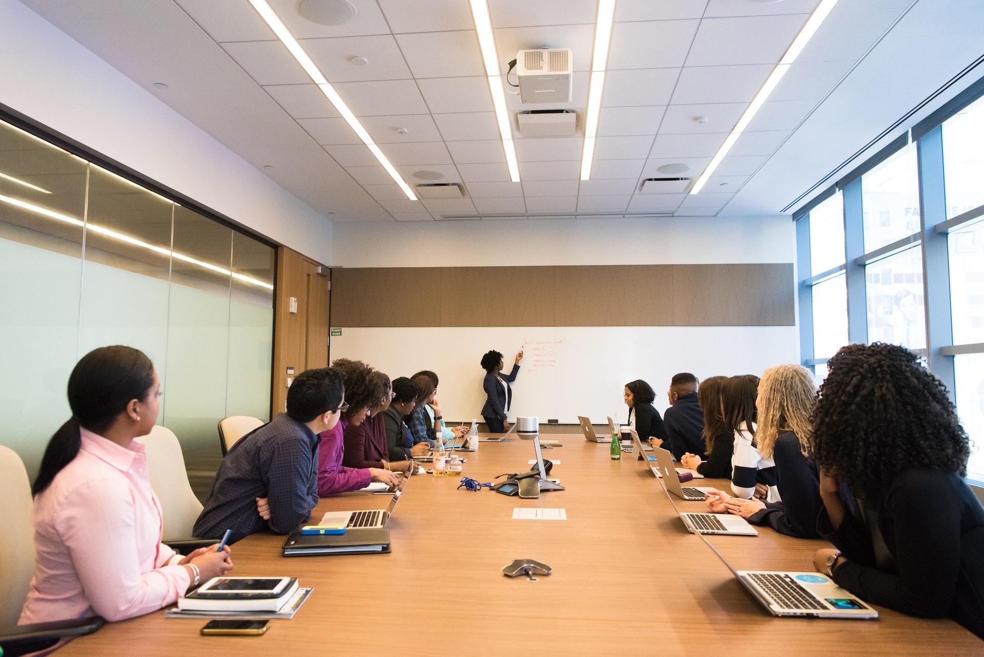 Vemos uma mulher dando uma palestra para outras em uma sala de reunião (imagem ilustrativa). Texto: feira de franquias.
