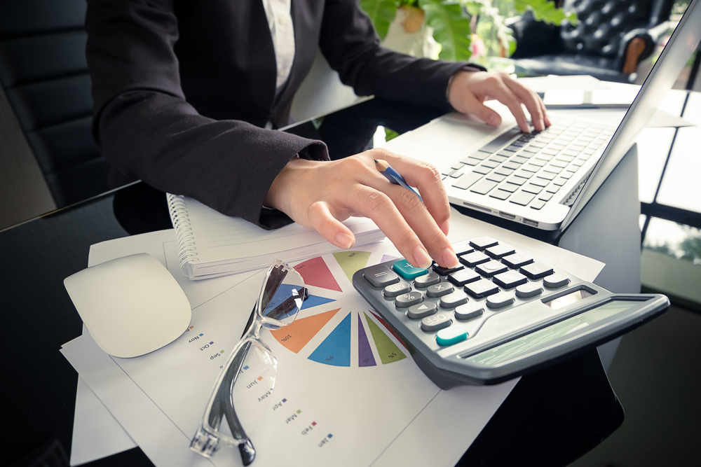 Vemos uma mulher trabalhando; sobre a mesa vemos planilhas, óculos, calculadora, notebook e caderno (imagem ilustrativa). Texto: franquia de empréstimos.