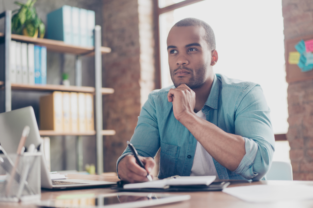 Vemos um homem fazendo alguns planejamentos em seu escritório (imagem ilustrativa). Texto: franquia de empréstimos.