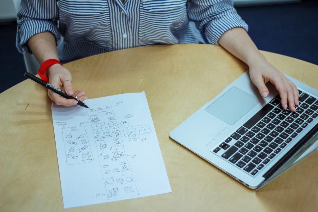 Vemos uma mulher fazendo algumas análises; vemos sobre a mesa papel e um computador (imagem ilustrativa). Texto: franquia de empréstimos.
